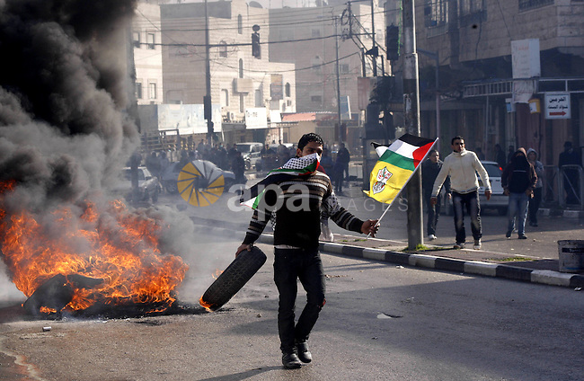 A Palestinian protester holds his national flag and a tyre during a demonstration against the closure of Shuhada street to Palestinians, in the West Bank city of Hebron February 24, 2012. Some 200 protesters, including foreign and Israeli activists, gathered on Friday marking the 18th anniversary of the closure of the street, which was closed by the Israeli army in 1994 following the Hebron mosque massacre by Baruch Goldstein, an Israeli settler, who went on a rampage inside Al Ibrahimi Mosque, killing 29 Palestinian worshippers. Photo by Mamoun Wazwaz