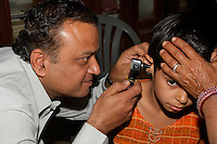 Doctor examining a young patient at the free medical clinic in Fort Dundlod, India.