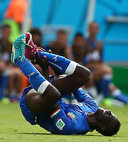 Mario Balotelli of Italy winces in pain as he goes down with an injury