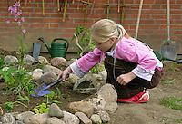 Schulgarten, Anlage eines Schmetterlingsgarten, Garten der Grundschule Nusse wird als Projektarbeit von einer 1. Klasse gestaltet, Beete werden in Form eines Schmetterlings angelegt und mit für Nektarliebende Falter wichtigen Blumen bepflanzt, Mädchen pflanzt, Gartenarbeit