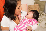 Sad crying 4 month old baby girl held by mother comforted