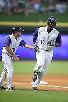 Keon Barnum (20) of the Winston-Salem Dash gets a slap on the back from third base coach Tim Esmay (10) as he rounds the bases after hitting a solo home run in the bottom of the fifth innings against the Wilmington Blue Rocks at BB&T Ballpark on July 30, 2015 in Winston-Salem, North Carolina.  The Dash defeated the Blue Rocks 7-3.  (Brian Westerholt/Four Seam Images)