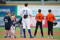 A group of youth baseball players stand on the mound with Burlington Royals starting pitcher Travis Eckert (23) during the National Anthem prior to the game against the Bluefield Blue Jays at Burlington Athletic Stadium on June 27, 2016 in Burlington, North Carolina.  The Royals defeated the Blue Jays 9-4.  (Brian Westerholt/Four Seam Images)