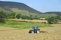 Tedding hay ready for baling on an organic farm at Whitewell, Clitheroe, Lancashire.