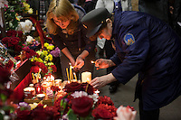 Moscow, Russia, 30/03/2010..A female Moscow Metro worker lights candles at a makeshift shrine on the spot inside Park Kultury metro station where a female suicide bomber blew herself up the previous day. At least 39 people were killed and 80 injured in the double blasts at Moscow metro stations during the morning rush hour.