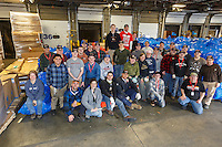 Getting ready for Iditarod 2016, over 30 volunteers take a break from straw drop day to gather for a group photo on Thursday, February 11, 2016  at Airland Transport in Anchorage.   Nearly 1700 bales will be sent out to over 20 checkpoints along the trail. Iditarod 2016