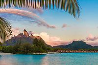 Sunrise on Mount Otemanu and overwater bungalows, on Bora Bora island, romantic honeymoon destination, near Tahiti, French Polynesia, Pacific Ocean