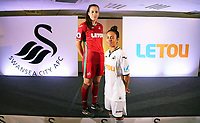 Pictured: Katy Hosford (RED) and Alicia Powe (WHITE) of the Swansea City FC Ladies' team model the home and away kits. Monday 19 June 2017<br />