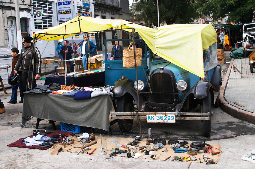 A market stall street market merchant selling various old stuff, mostly looking like leftover bits and pieces of junk. and A classic old car Overland Whippet from Willys Overland Whippet Limited, Canada, Montevideo, Uruguay, South America