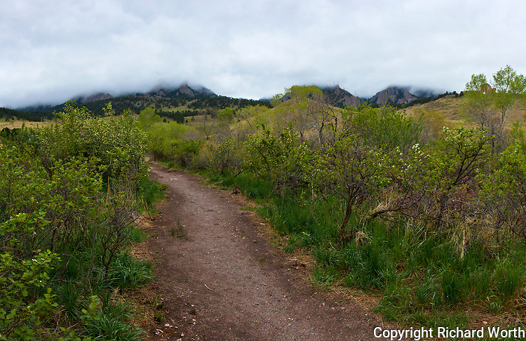 Ominous clouds cover the foothills ahead, including Bear Peak, along Bear Canyon Trail in Boulder, Colorado.