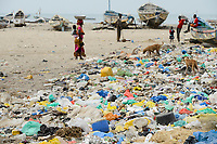 SENEGAL, Joal, coast fisherman, wooden boats at shore of atlantic ocean, plastic garbage / Küstenfischer und Holzboote am Atlantik