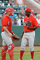 Victor Alcantara (46) of the Orem Owlz and catcher Zac Livingston (15) meet at the mound in action against the Ogden Raptors at Lindquist Field on July 05, 2013 in Ogden Utah. (Stephen Smith/Four Seam Images)