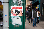 """BROOKLYN, NY — OCTOBER 27, 2020:  A sign critical of NY Governor Andrew Cuomo and NYC Mayor Bill de Blasio reading """"dumb and dumber"""" is posted to a utility pole next to people waiting in line to vote around the corner from the Park Slope Armory during early voting for the 2020 U.S. presidential election on October 27, 2020 in the Brooklyn borough of New York City.  Photograph by Michael Nagle"""