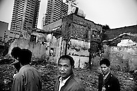 Men walk past destroyed hutongs, or traditional Chinese residential alleys, in central Tianjin, China, which have been demolished to make room for modern high-rise building construction.
