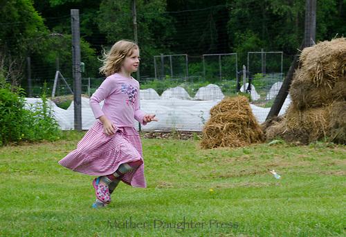 Young girl runs in the the garden, YCG, Maine, USA