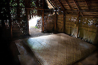 Recreated Hawaiian hut used as a sleeping house with lauhala mat bed at Kamokila Hawaiian Village, Wailua River Valley, Kauai.