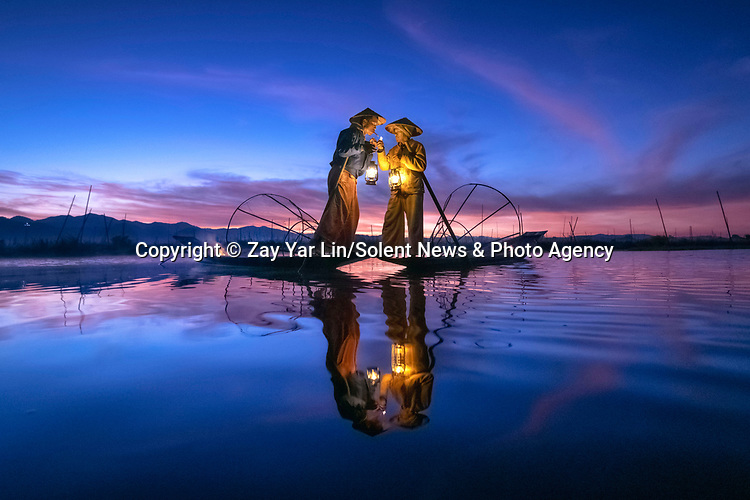 Fishermen are illuminated by candle light as they start their day at sunrise.  The men, standing on their small wooden boats, huddle together as they hold lanterns.<br /> <br /> The fishermen then skillfully balance on one leg and use the other to carry a conical fishing net whilst looking for fish to catch.  Amateur photographer Zay Yar Lin pictured the fishermen on Inle Lake, Myanmar.  SEE OUR COPY FOR DETAILS.<br /> <br /> Please byline: Zay Yar Lin/Solent News<br /> <br /> © Zay Yar Lin/Solent News & Photo Agency<br /> UK +44 (0) 2380 458800