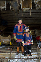 Jouana and his grandfather Esa, Sami reindeer herders in Lapland, Arctic Circle, Finland.<br /> Sami are the indigenous people of the Scandinavian Arctic that includes the northernmost areas of Finland. Jouana is following in his father's and grandfather's footsteps as he ran out into the snow to feed the reindeer on their farm.