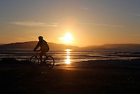 Swansea, UK. Saturday 21 June 2014<br /> Pictured: A cyclist rides on the Swansea Bay cycle path near Mumbles as the sun rises over the city marking the Summer Solstice and the year's longest day.