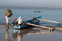 Jimbaran Beach, Bali, Indonesia.  Bringing Baskets to the Boat before Going out to Fish.