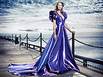 Young woman wearing a beautiful long blue evening gown standing at waterfront, artistic fashion portrait Image © MaximImages, License at https://www.maximimages.com