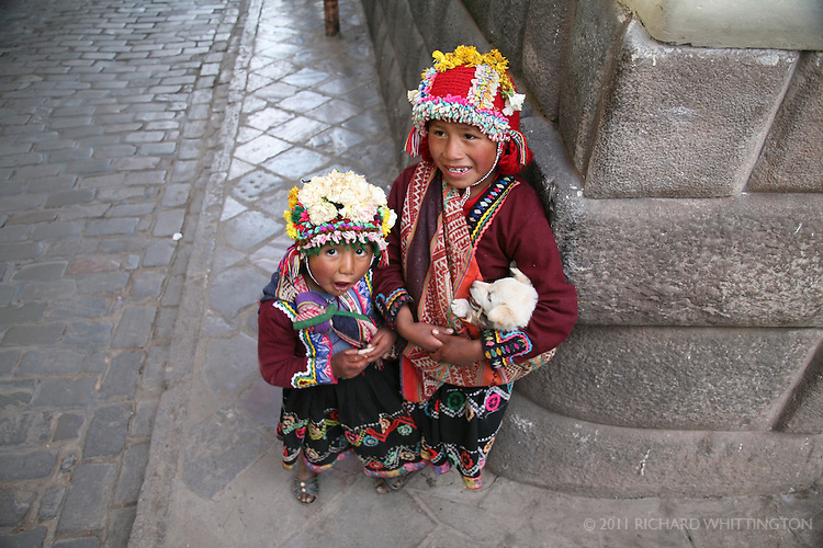 Two young peruvian boys stand on the corner of a street in Cuzco.