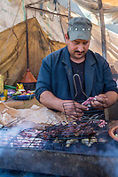 Morocco.  Vendor Grilling Brochettes (Shish-kebabs), Had Draa Market, Essaouira Province.