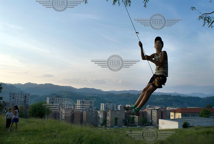 A boy plays on a rope swing in the hills above a housing estate in the town of Vulcan.