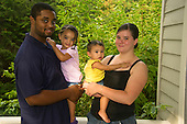 MR / Schenectady, NY. Family portrait outside on porch. From left to right; father (22, African American), daughter (2, African American & Caucasian), infant daughter (girl, 10 months, African American & Caucasian), and mother (20). MR: Dal7, Dal5, Dal4, Dal6. ID: AL-HD. © Ellen B. Senisi