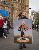 Political satire artist Kaya Mar poses with his artwork of Prime Minister Theresa May playing the violin with one foot on a coffin titled Brexit  - BREXIT scenes in Westminster Houses of Parliament and surrounding area, London, England on 16 January 2019. Photo by Andy Rowland.