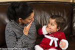 12 month old baby girl sitting on grandmother's lap imitating her gesture of blowing a kiss