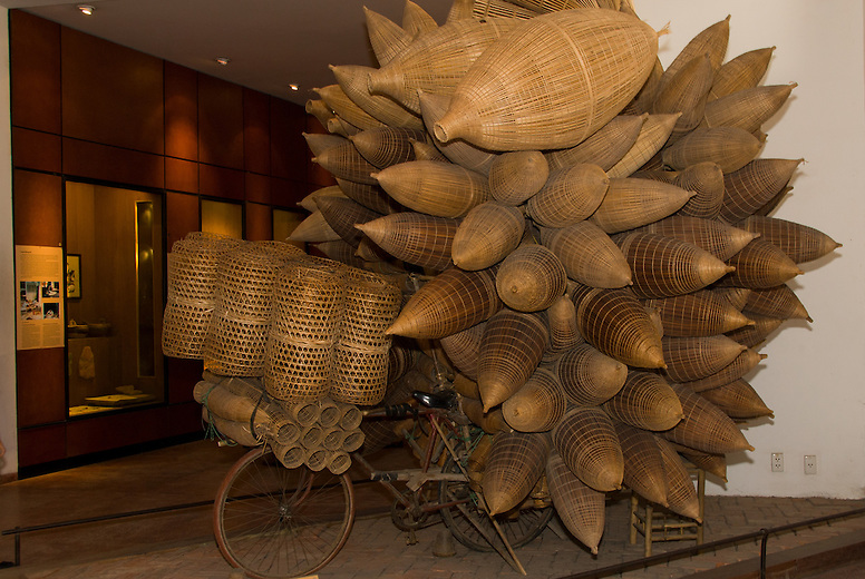 Bikes used to be the main form of transportation as shown in this exhibit at the Museum of Ethnology in Hanoi, Vietnam.  Motorbikes have taken the lead and have resulted in an increase in pollution in the cities. A variety of goods are being carried by bikes including these traditional fish nets.