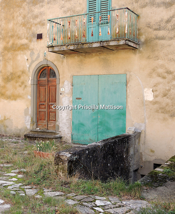Val d'Arno, Italy - October 5, 2012:  Turquoise paint accents a rustic Tuscan home.