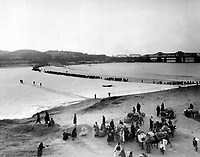 Refugees streaming across the frozen Han River on the ice as they flee southward before the advancing tide of Red Chinese and North Korea Communists.  Shattered bridges are shown in the background.  January 1951.  INP. (USIA)<br /> Exact Date Shot Unknown<br /> NARA FILE #:  306-PS-52-2719<br /> WAR & CONFLICT BOOK #:  1478