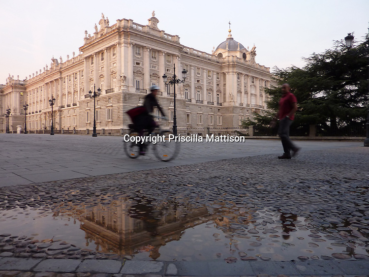 Madrid, Spain - October 16, 2011:  A bicyclist and a pedestrian are reflected in a puddle as they pass in front of the Palacio Real de Madrid in early morning.