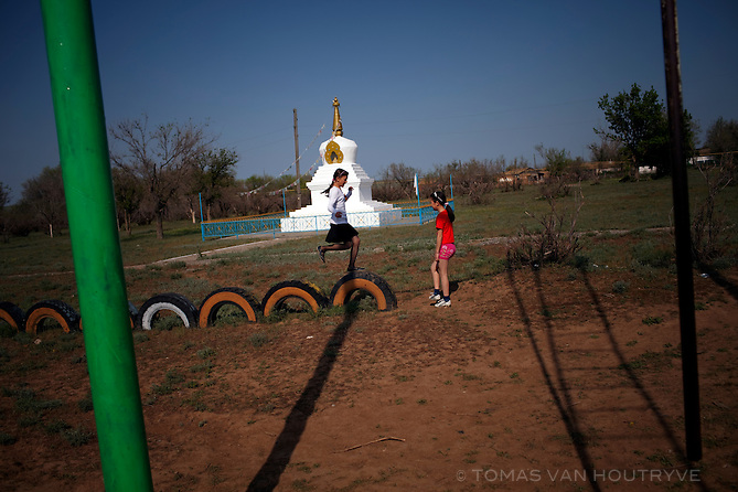Girls play in a playground in the village of Arshan Bulg, Republic of Kalmykia, Russian Federation on May 8, 2010. Seen in the background is a Buddhist stupa.