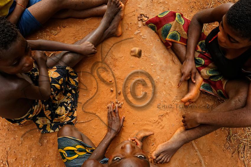 On the laterite track, the children play a type of jacks with little stones, the Lopli.///Les enfants jouent sur la piste en latérite avec des cailloux une forme sophistiquée d'occelets, le Lopli.