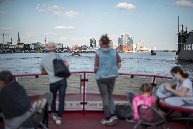 Menschen fahren bei sonnigem Fruehlingswetter im Hamburger Hafen auf einer Linien-Faehre der Hamburger Verkehrsbetriebe. Der Linenverkehr wird von vielen Menschen als guenstige Alternative fuer eine Hafenrundfahrt genutzt.<br /> Im Hintergund die Skyline von Hamburg mit der Elbphilharmonie.<br /> 9.5.2020, Hamburg<br /> Copyright: Christian-Ditsch.de<br /> [NUR FUER REDAKTIONELLE ZWECKE! Werbung nur auf Anfrage beim Fotografen.Inhaltsveraendernde Manipulation des Fotos nur nach ausdruecklicher Genehmigung des Fotografen. Vereinbarungen ueber Abtretung von Persoenlichkeitsrechten/Model Release der abgebildeten Person/Personen liegen nicht vor. NO MODEL RELEASE! Don't publish without copyright Christian-Ditsch.de, Veroeffentlichung nur mit Fotografennennung, sowie gegen Honorar, MwSt. und Beleg. Konto: I N G - D i B a, IBAN DE58500105175400192269, BIC INGDDEFFXXX, Kontakt: post@christian-ditsch.de<br /> Bei der Bearbeitung der Dateiinformationen darf die Urheberkennzeichnung in den EXIF- und  IPTC-Daten nicht entfernt werden, diese sind in digitalen Medien nach §95c UrhG rechtlich geschuetzt. Der Urhebervermerk wird gemaess §13 UrhG verlangt.]