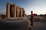 A male tourist wearing a hat and red shirt visits the Ramesseum, or memorial temple of Ramses II, on the West Bank of Luxor, Egypt, near the Nile River.