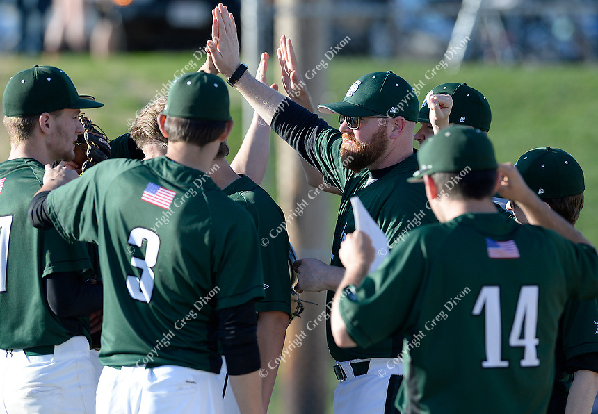 Head coach, Tim Richardson, high fives Madison Memorial players, as Memorial tops West 2-0 in Big Eight Conference high school baseball on Tuesday, 4/23/19 at Mansfield Stadium field at Memorial High School in Madison, Wisconsin