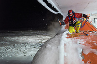 A member of deck crew clears ice from the exterior of the icebreaker and supply ship the 'Fedor Ushakov' as it makes its way through the Barents Sea along the Northern Sea Route.<br />