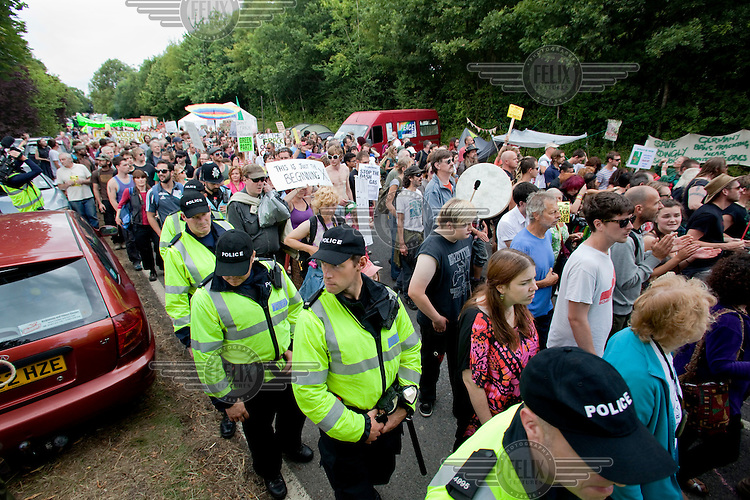 Police officers oversee an anti fracking demonstration in Balcombe, West Sussex. The protesters at Balcombe in West Sussex are worried about the environmental effects of hydraulic fracturing (or fracking) which involves injecting a mixture of water, chemicals and sand into shale rock in order to extract oil and gas trapped below ground. They have been joined by anti fracking demonstrators from across the UK and Ireland. The energy company Cuadrilla is prospecting for oil and gas in West Sussex and the protesters are keen for the company to stop its operations to preserve the natural environment.