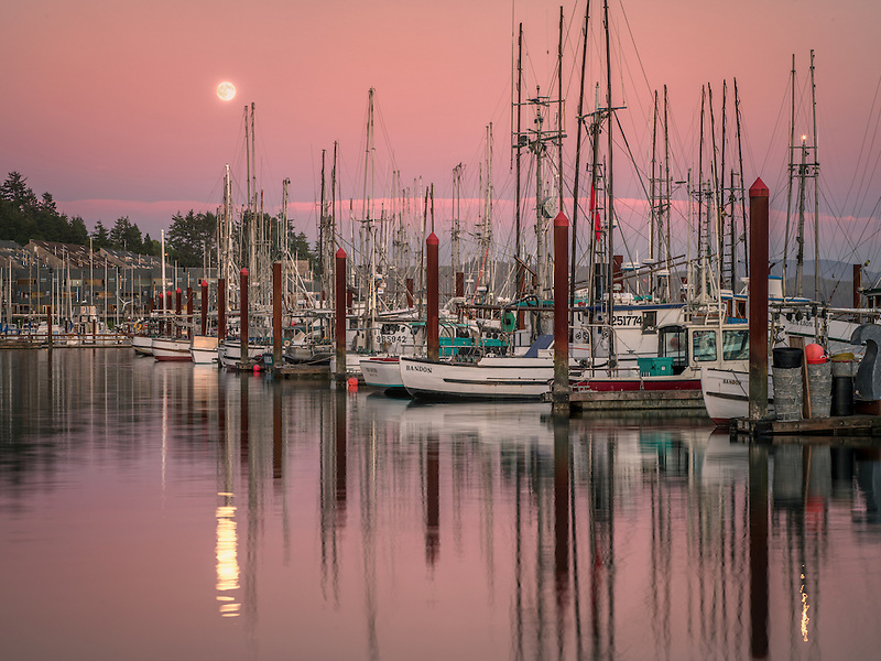 Moon set over Newport Harbor with fishing boats. Newport, Oregon