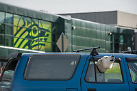 A husky howls for the home team in front of the spine connecting UAA's Rasmuson Hall and Wells Fargo Sports Complex.