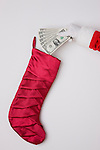 USA, Illinois, Metamora, Studio shot of Santa's hand putting fan of one dollar banknotes into Christmas stocking