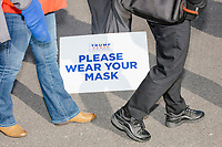 """A campaign worker stands near a Trump campaign sign reading """"Please wear your mask"""" as he hands out masks to those in line to enter a Make America Great Again Victory Rally with US President Donald Trump in the final week before the Nov. 3 election at Pro Star Aviation in Londonderry, New Hampshire, on Sun., Oct. 25, 2020. Many wore MAGA hats and other Donald Trump paraphernalia. Encouraging mask wearing is a complete reversal of the first six months of the Trump administration's approach to the ongoing Coronavirus (COVID-19) global pandemic."""