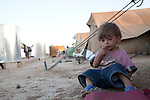 DOMIZ, IRAQ: A child sits outside a tent in the Domiz refugee camp..Over 7,000 Syrian Kurds have fled the violence in Syria and are living in the Domiz refugee camp in the semi-autonomous region of Iraqi Kurdistan...Photo by Ali Arkady/Metrography