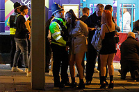 Pictured: A young woman is spoken to by a police officer in Swansea. Tuesday 31 December 2019 to Wednesday 01 January 2020<br /> Re: Revellers on a night out for New Year's Eve in Wind Street, Swansea, Wales, UK.