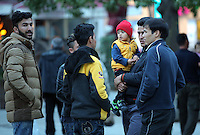 Pictured: Migrant men with a young boy held by one of them Wednesday 09 March 2016<br /> Re: Migrants at Victoria Square, in central Athens, Greece.