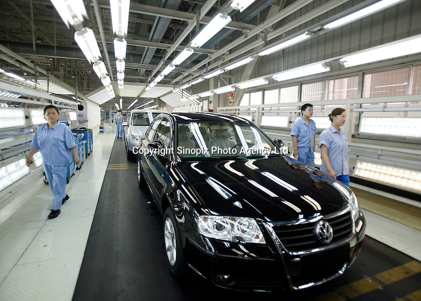Workers examine finished cars at the Shanghai Volkswagen (SVW) plant in Shanghai, China..